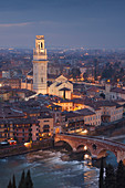 View from Castel San Pietro over the illuminted oldtown of Verona with the tower of the cathedral Santa Maria Matricolare and Ponte Pietra bridge over the Adige, Veneto, Italy