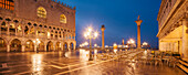 Panorama of St. Mark's Square with the illuminated facade of the Doge's Palace, lanterns and columns with Markus Lion and the San Todaro statue in blue night, Biblioteca Nazionale Marciana right, Church of San Giorgio Maggiore in the background, Piazzetta