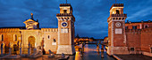 Panorama of the Arsenale di Venezia, the former shipyard and naval base in the blue of the night, with an illuminated wall and portal Ingresso di Terra left and Ingresso All'Acqua at the right, Venetian Arsenal, Castello, Venice, Veneto, Italy