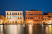 Overlooking the Grand Canal with the illuminated facades of the Palazzo Dolfin Manin and the Palazzo Bembo (from left) in the blue dusk, San Marco, Venice, Veneto, Italy