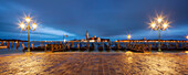 Panoramic view from St. Mark's Square with gondolas and lanterns to the island of San Giorgio Maggiore with its namesake church in the blue of the night, San Marco, Venice, Veneto, Italy