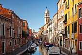 Houses on the Rio di San Barnaba with the tower of the church of Santa Maria dei Carmini and boats in the morning sun and blue sky, Dorsoduro, Venice, Veneto, Italy