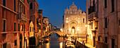 Panorama on the canal Rio dei Mendicanti with illuminated Scuola Grande di San Marco, the historic facade of the Ospedale hospital and boats in the blue dusk, Sestiere Castello, Venice, Veneto, Italy