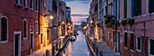 Panorama of illuminated houses and boats at Rio de la Fornace in the blue dawn, Dorsoduro, Venice, Veneto, Italy