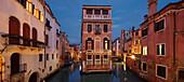 Panorama overlooking a illuminated house between channels Rio di San Giovanni Laterano and Rio de la Tetta in blue twilight, Castello, Venice, Veneto, Italy