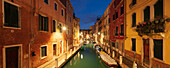 Panorama of illuminated house facades and boats on the canal Rio Ognissanti in blue twilight, Dorsoduro, Venice, Veneto, Italy