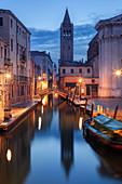 Illuminated houses of the Rio di San Barnaba with the tower of the church of Santa Maria dei Carmini and boats in the blue dusk, Dorsoduro, Venice, Veneto, Italy