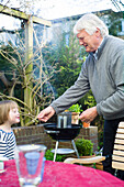 Granddaughter und grandfather blowing matches, Hamburg, Germany