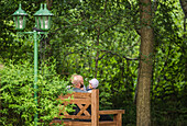 Father and two children sitting on a bench in the garden, Holiday, Vacation, Summer, Spreewald, Oberspreewald, Brandenburg, Germany