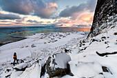 Fotograf auf dem Schnee bewundert das Fischerdorf unter einem bunten Himmel Eggum, Vestvagoy (Vest-Vagoy) Insel, Lofoten Inseln, Arktis, Norwegen, Skandinavien, Europa