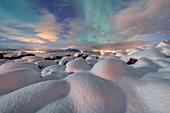 The pink light and the aurora borealis (Northern Lights) illuminate the snowy landscape on a starry night Stronstad, Lofoten Islands, Arctic, Norway Scandinavia, Europe