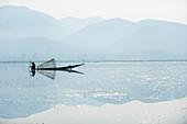 Ein Korbfischer auf Inle See scannt das ruhige und flache Wasser für Zeichen des Lebens, Shan State, Myanmar (Burma), Asien