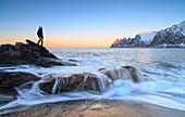 Wanderer bewundert die Wellen des eisigen Meeres, das auf den Felsen im Morgengrauen, Tungeneset, Senja, Troms Grafschaft, Arktis, Norwegen, Skandinavien, Europa, zusammenstürzt