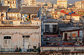 A man comes out of his rooftop home in the early morning light in Havana, Cuba, West Indies, Caribbean, Central America