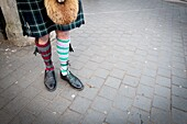 Unrecognizable man wearing typical Scottish costume and 'odd socks'. London, England