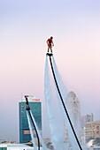 UAE, Dubai, Dubai Marina, Jumeirah Beach, water jet pack stunt flyers, dusk.