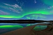 Aurora borelais (Northern Lights) over Pine Lake in moonlight, Wood Buffalo Ntional Park, Alberta, Canada.