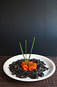 Black spaghetti with smoked salmon and chives.