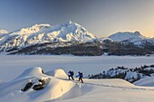 Snowshoe hikers explore the winter landscape in Engadine. Switzerland.