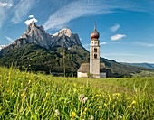 Kastelruth / Castelrotto, Dolomites, South Tyrol, Italy. The church of St. Valentin in Kastelruth/Castelrotto. In the background the jagged rocks of the Schlern/Sciliar.