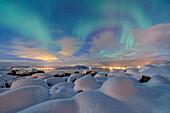 The pink light and the aurora borealis illuminate the snowy landscape on a starry night Strønstad Lofoten Islands Norway Europe.
