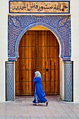 Fes, Marocco, North Africa. Woman with blue traditional dress in front of a typical moroccan door.