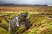 Waterfall at Hull Pot with Pen Y Ghent Shrouded in Low Cloud Horton in Ribblesdale North Yorkshire England.