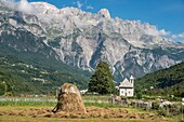 Looking across the village of Theth with its shingle roofed church and the Albanian Alps, Radohima massif and Mount Arapit in the background, Northern Albania.