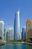 Daytime skyline view of Almas Tower and modern high-rise office and apartment buildings at JLT, Jumeirah Lakes Towers in Dubai United Arab Emirates.