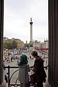 Paar blickt von der Terrasse der National Gallery auf das Treiben des Trafalgar Square, dahinter Whitehall und Big Ben, London, England
