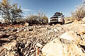 All-terrain vehicle descending slowly a rocky slope, Kunene, Namibia, Africa
