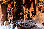 Young Himba man in his hut, Kunene, Namibia, Africa