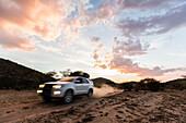 All-terrain vehicle at dusk on a dirt road in Damaraland, Kunene, Namibia