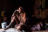Himba woman in her hut, Kunene, Namibia