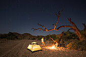 Two men at a camp fire in the Doros dry river bed, Damaraland, Kunene, Namibia