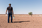 A man reflecting upon his toilet options. What's not buried carefully, will be dug out by wild animals, and due to the dry climate, things decompose extremely slowly. Paper has to be burned. Damaraland, Erongo, Namibia, Africa