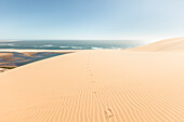 Footprints in the dunes high above the lagoons of Sandwich Harbour, Walvis Bay, Erongo, Namibia, Africa.