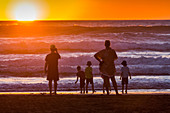 family on surf beach, silhouettes against sunset, backlit, west coast, North Island, New Zealand
