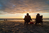 couple sitting in camping chairs on beach, sunset, west coast, Hokitika, South Island, New Zealand