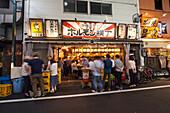 Japanische Kneipe am Abend mit jungen Leuten die zusammen essen und trinken, Shinjuku, Tokio, Japan