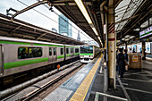 Passengers waiting for train of Yamanote Line on track at Shinjuku Station, Shinjuku, Tokyo, Japan