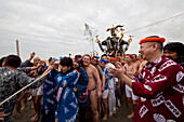 Men dressed in Fundoshi and women dressed in yukata carrying Omikoshi during Seijin-Sai-Festival at Enoshima beach, Fujisawa, Kanagawa Prefecture, Japan