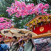 Two men with umbrellas in front of decorated festival wagon during Yayoi Matsuri in Nikko, Tochigi Prefecture, Japan