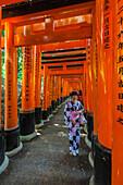 Young woman dressed in kimono at stone path with many red Torii at Fushimi Inari-Taisha in Kyoto, Japan