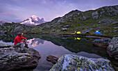 Wanderer mit einer Stirnlampe an den Lacs des Cheserys, Zelte, Aiguille Verte, Haute-Savoie, Frankreich
