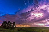 A massive thunderstorm moves across the northern horizon lit internally by lightning. The clear sky behind it is lit blue from the perpetual twilight of summer solstice. This was on Friday, June 20, the night before solstice. This is a single exposure of
