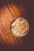 Top down view on a plastic cup filled with ice coffee on wooden bench. Beverage copyspace.