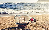 Ship in a bottle on sandy beach with foaming waves and mountain in background for concept about travel and adventure.