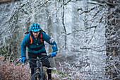 Junger Mann fährt mit seinem Fahrrad durch einen mit Frost bedeckten Wald, Allgäu, Bayern, Deutschland