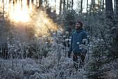 Junger Läufer streht in einen mit Frost bedeckten Wald, Allgäu, Bayern, Deutschland